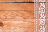 Beautiful white lace with floral ornament on wooden boards.