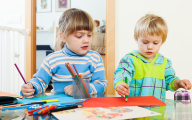 serious children sketching with paper and pencils