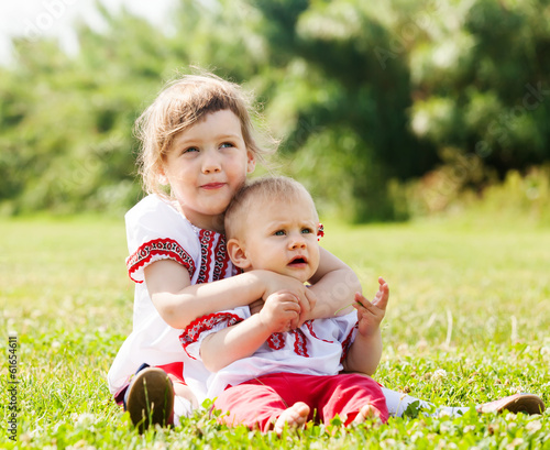 children in traditional  clothes on grass