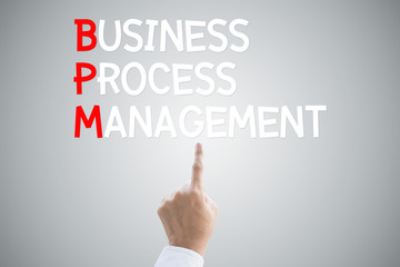 Business process management hand press concept on grey backgroun