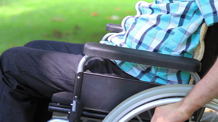 Young man in a wheelchair in the park