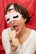 Attractive woman in sleeping mask imitates singing into a microp