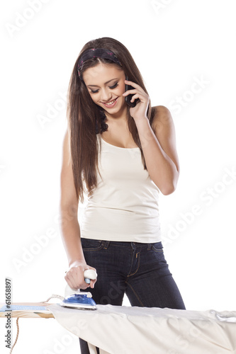 young smiling girl ironing and talking on the phone