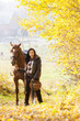 canvas print picture - equestrian with her horse in autumnal nature