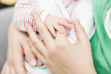 Mother holding newborn baby hand