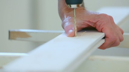 drilling holes in the wooden board electric drill