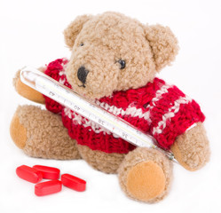 Sick teddy bear with thermometer isolated on white