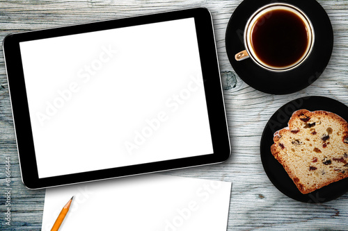 workplace with digital tablet, notebook, cake and coffee cup