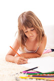 Cute little girl drawing with color crayons on the floor.