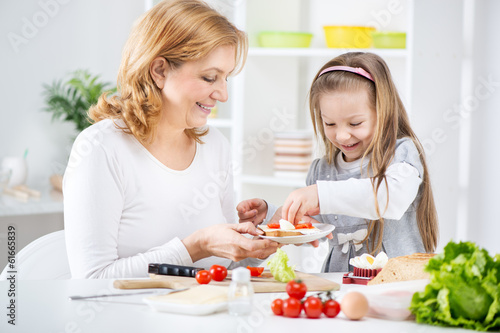 Grandmother and her granddaughter making Sandwich.