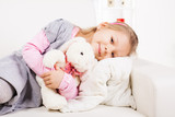 Cute little girl hugging soft toy on sofa at home.