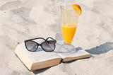 Book, orange juice and sunglasses on a beach
