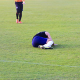Soccer player lying down on football match