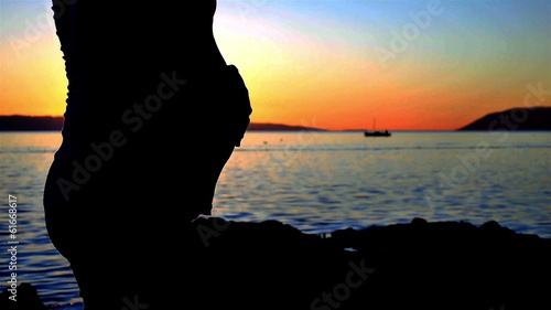Silhouette of pregnant woman touching belly near sea in sunset