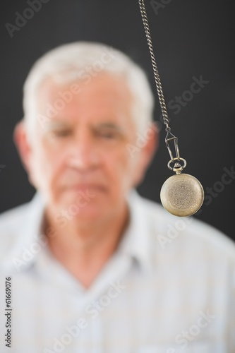 Senior man being hypnotized with pendulum
