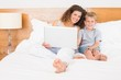 Happy mother and son sitting on bed using laptop