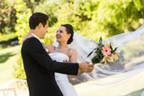 Cheerful newlywed couple dancing in park