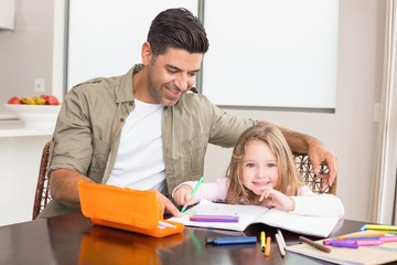 Cheerful little girl colouring at the table with her father