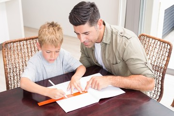 Handsome father helping son with homework at table