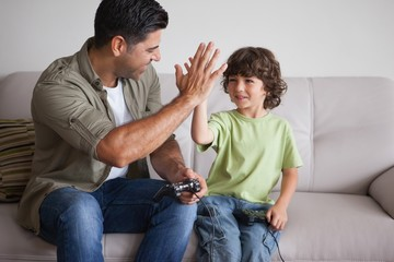 Father and son playing video games in living room