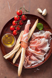 italian prosciutto ham grissini bread sticks tomato olive oil