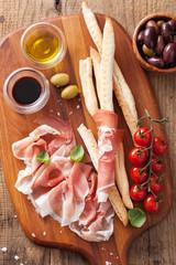 italian prosciutto ham grissini bread sticks tomato olive oil