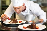 Concentrated male pastry chef decorating dessert