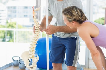 Trainer showing model of spinal cord to woman