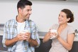 Attractive couple sitting having coffee together and laughing