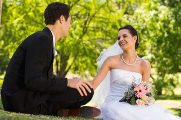 Happy newlywed couple sitting in park