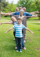 Extended family standing in row with arms outstretched at park