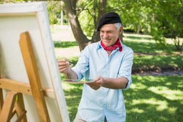 Mature man painting in park