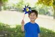 Happy cute little boy holding pinwheel at park - 61672219
