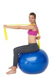 Full length portrait of fit woman exercising on fitness ball