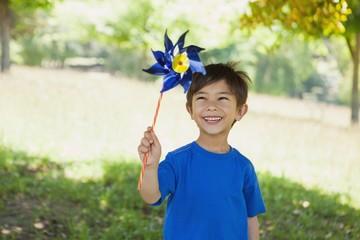 Happy cute little boy holding pinwheel at park