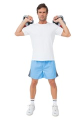 Full length portrait of a fit man lifting kettlebells