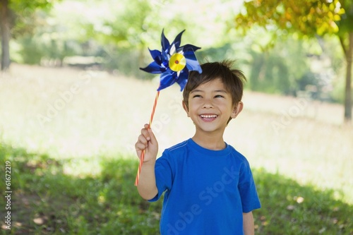 Happy cute little boy holding pinwheel at park