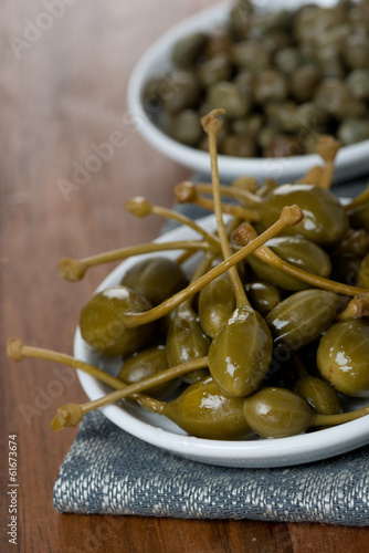 two kinds of pickled capers on wooden table