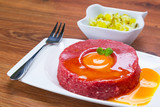 Tasty steak tartare on the plate with egg yolk