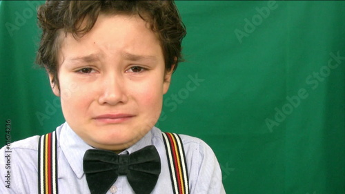 Boy crying  in front of a green screen
