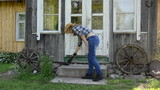 Worker woman clean sweep stairs with wooden broom in rural yard
