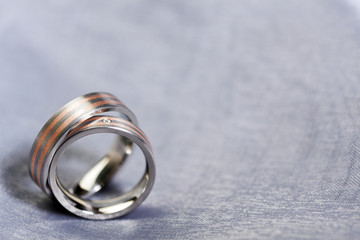 Wedding rings on silver cloth with copy space