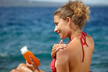 woman applying sun protection lotion