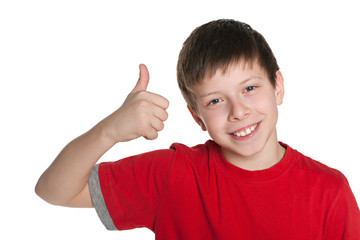 Preteen boy in the red shirt holds his thumb up