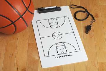 A basketball with coach's clipboard and whistle on a wooden gymn