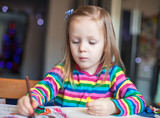 Adorable little girl draws paints sitting at the table