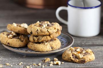 Kekse auf einem Teller und ein Kaffeebecher im Hintergrund