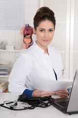 Junge Ärztin sitzend am Schreibtisch - in weißer Kleidung