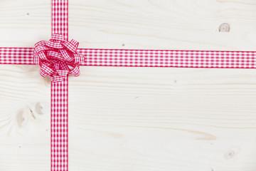 Holzhintergrund mit rot-weißem Stoffband und Schleife