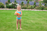 Little adorable girl playing with water gun outdoor in sunny